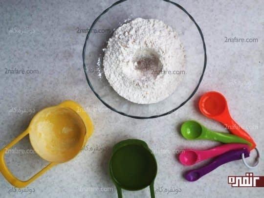 شکر و نمک رو هم وسط آرد میریزیم و مخلوط میکنیم مواد خشک رو