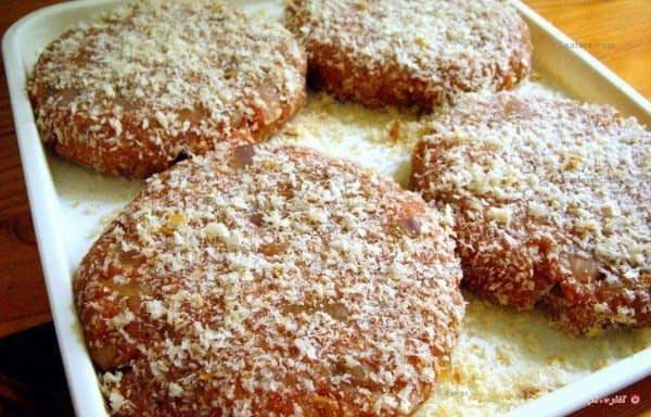 پنیر پارمسان روی همبرگرهای آماده ی پخت