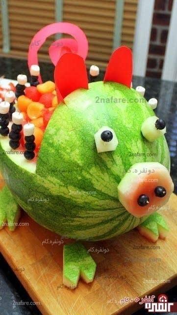خوک هندوانه ای همراه با تزئین های انگور سیاه و دیگر میوه ها