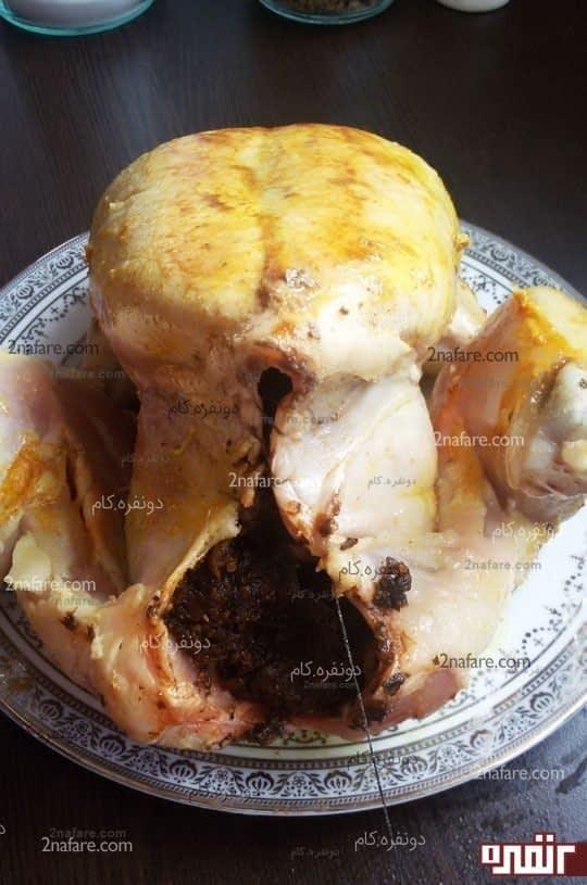 بعد از ریختن مواد شکم مرغ رو با نخ و سوزن بدوزید