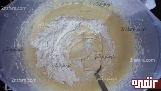 افزودن آرد به مواد برای تهیه ی کیک زبرا