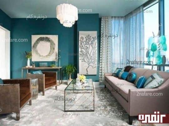 دیوارهایی با رنگ آبی کله غازی به همراه وسایل تزیینی آبی ملایم و مبلمانی با تناژ قهوه ای روشن.ترکیب رنگ اجزاء و چیرمان می تواند فضای اتاق نشیمن شما رو آرامش بخش و راحت جلوه بده.