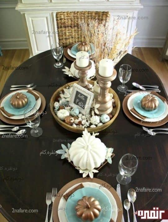 ترکیب رنگ قهوه ای میز ناهارخوری با پیش دستی های آبی و شمع های سفید و جا جشمعی های انتیم مسی رنگ و گلدان سفید همراه با گندم که هارمونی جذاب و سردی رو ایجاد خواهد کرد