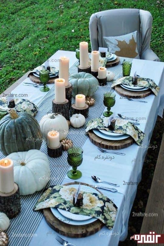 چیدمانی مانند قرار دادن کدو تنبل های سفید و سبز در میانه میز همراه با شمع هایی که جا بر روی برشی از یک قطعه چوب طبیعی قرار دارند و دستمال سفره هایی مزین به گل هایی که با رنگ های به کار رفته تناسب رنگی دارند