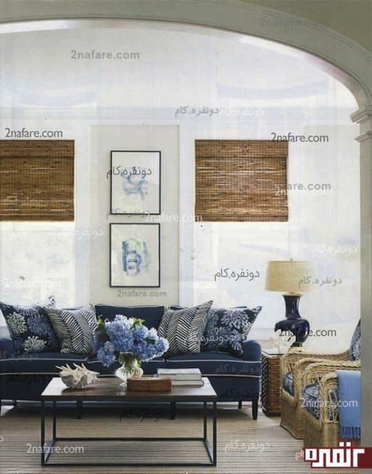 طراحی یک اتاق نشیمن با نمایی شبیه به یک کلبه ساحلی با انتخاب رنگ ماسه ای برای دیوارها ویک آباژور که کلاهه اش بامبو رنگ است،پشتی های روی مبل که به آبی کبود است به همراه را های سفید رنگی که به زیبایی بیشتر اون ها کمک کرده ،میز پذیرایی به سبک بریک مارکر و صندلی های حصیری شکل