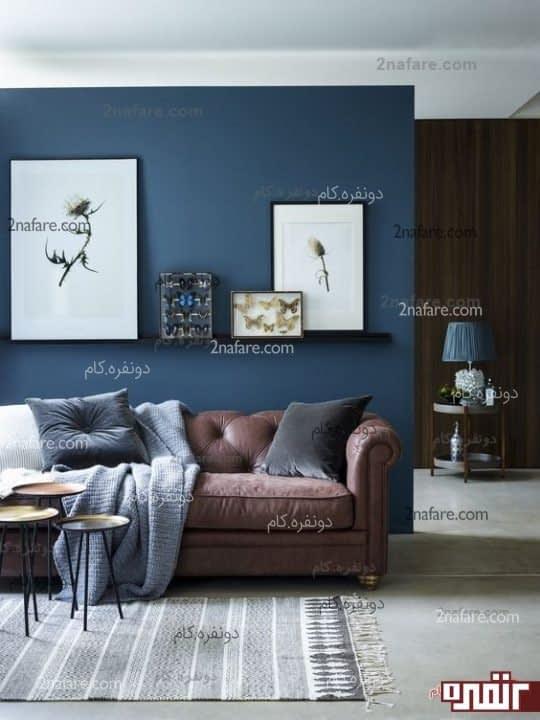 یک فضای نشیمن شیک با انتخاب رنگ دیواری که به رنگ آبی کاربنی است و یک کاناپه شکلاتی رنگ همراه با کوسن هایی که رنگ میانه ای از هر دو رنگ است.