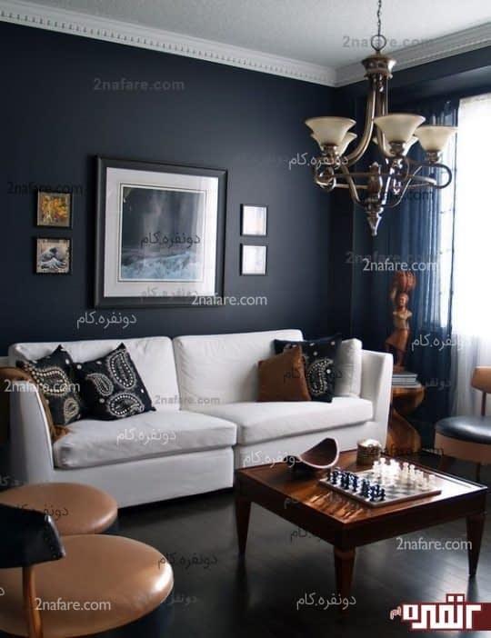 اتاق نشیمن با فضای خنثی و رسمی با انتخاب رنگ آبی متمایل به سرمه ای همراه با میز و صندلی های برنز رنگ به همراه وسایل و تزئیناتی که در انه ها طیف های رنگی گرم مشاهده میشود.