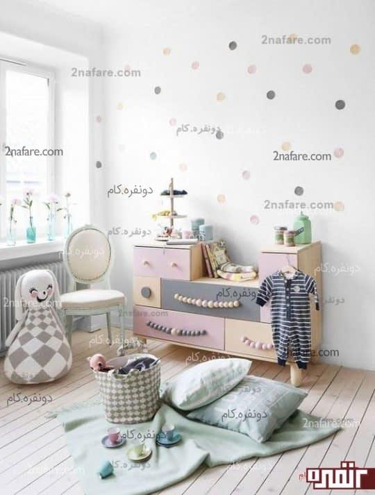 ایده یک میز به همراه کمد چوبی پادیواری با رنگ پاستلی مناسب برای اتاق دختر بچه ها که هارمونی و تناسب رنگ هم در ان رعایت شده است