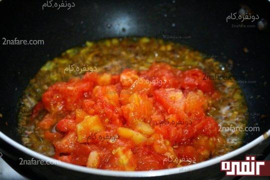 اضافه کردن گوجه فرنگی به پساز و سیر سرخ شده