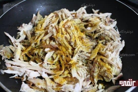 اضافه کردن ادویه به مخلوط گوشت مرغ و پیاز داغ