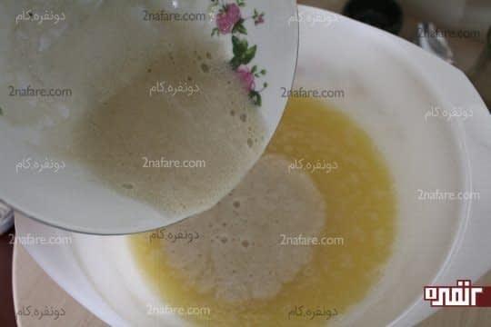 اضافه کردن خمیر مایه به مخلوط شیر و تخم مرغ و شکر
