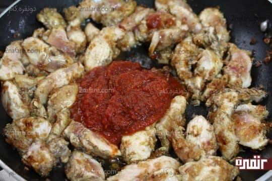 اضافه کردن رب گوجه فرنگی به مرغ تفت داده شده.