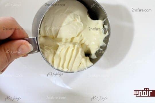 ریختن پنیر خامه ای در ظرف