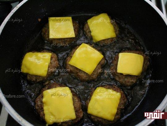 قرار دادن پنیر ها روی همبرگرها قبل از پخت نهایی
