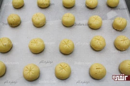 فرم دادن خمیر به صورت توپ های کوچک و طرح انداختن روی آنها