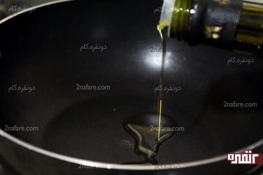 ریختن روغن زیتون در تابه