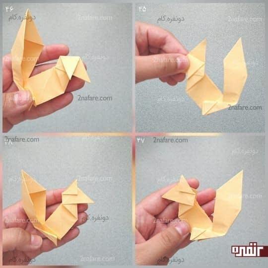 برای گوش هایش، گوشه های بالای دو مثلثی که در بالا و سمت چپ کار درست شده را مانند شکل به سمت پایین تا کنید