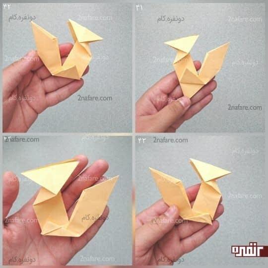 گوشه بالایی مثلث را به سمت ضلع پایین مثلث بیاورید و مانند شکل تا کنید