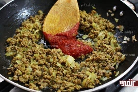 اضافه کردن رب گوجه فرنگی به کوشت و پیاز تفت داده شده