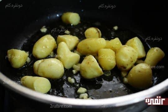 اضافه کردن سیب زمینی ها به سیر در حال تفت دادن