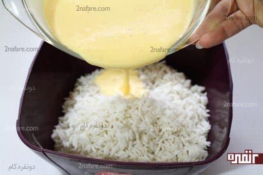 اضافه کردن مایه تهچین به برنج آپخته و آبکش شده