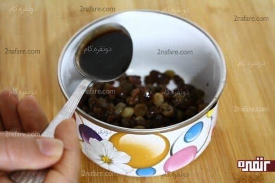 افزودن سویا سس به کشمش های خیس خورده و آبکش شده