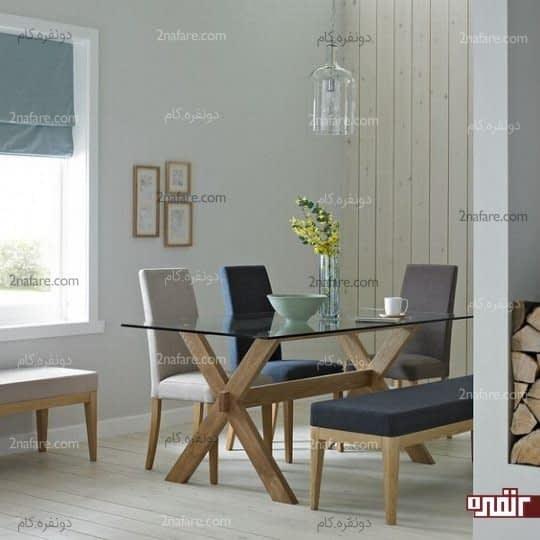 دیزاینی شیک و زیبا با میز شیشه ای پایه چوب در کنار صندلی و نیمکت های جذاب