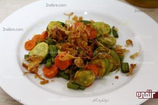 ریختن یک لایه از مخلوط سبزیجات و پیاز داغ