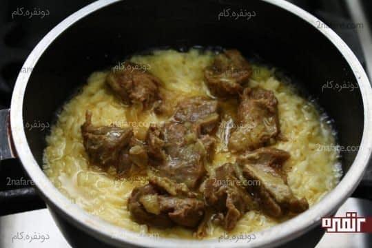 ریختن یک لایه مخلوط برنج کف قابلمه و یک لایه گوشت روی مایع تهچین