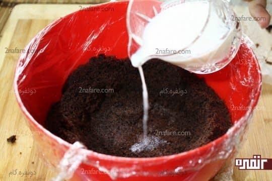 قرار دادن لایه اول کیک کف کاسه و مرطوب کردن کیک با شیر