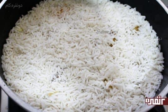 ریختن مابقی برنج آبکش شده روی بادمجان ها