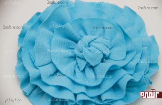بریدن پارچه اضافی دور گره و چسبوندن وسط گل پارچه ای