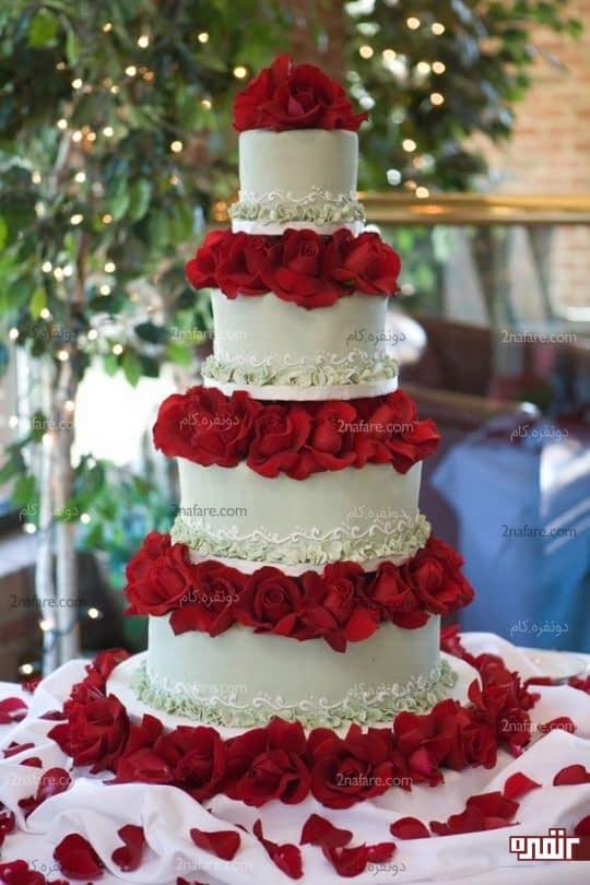 نیم طبقه ای از گل رز قرمز بین طبقات کیک عروسی
