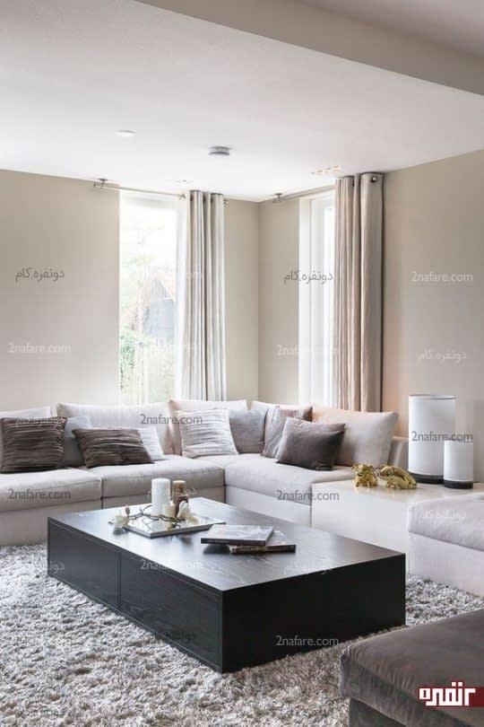 پنجره های قدی، میز قهوه خوری چوبی و فرش کرکی در اتاق نشیمن به سبک مدرن