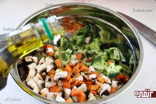آغشته کردن سبزیجات با روغن زیتون و نمک و فلفل