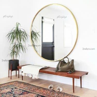 آینه با قابی طلایی و پس زمینه ی خنثی