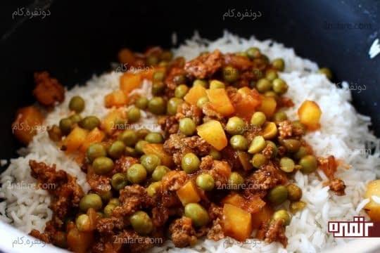 ریختن یک لایه از سس گوشت و نخود فرنگی روی برنج ابکش کرده