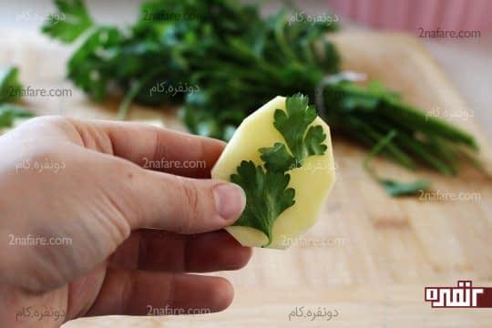 قرار دادن برگ ها جعفری روی سیب زمینی ها