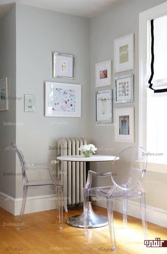 چیدمان زیبا برای کنج خانه با قراردادن میز و صندلی و تابلو های هنری