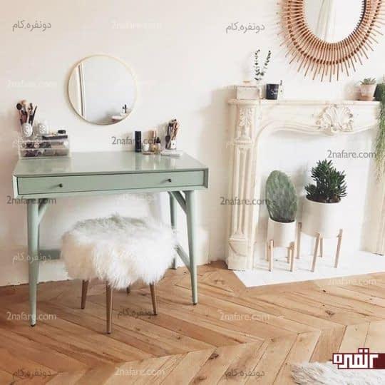 آینه ساده گرد در کنار میز و صندلی شیک آرایش