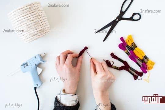 بستن قسمت بالای رشته نخ های رنگی برای ساخت منگوله ی رنگی
