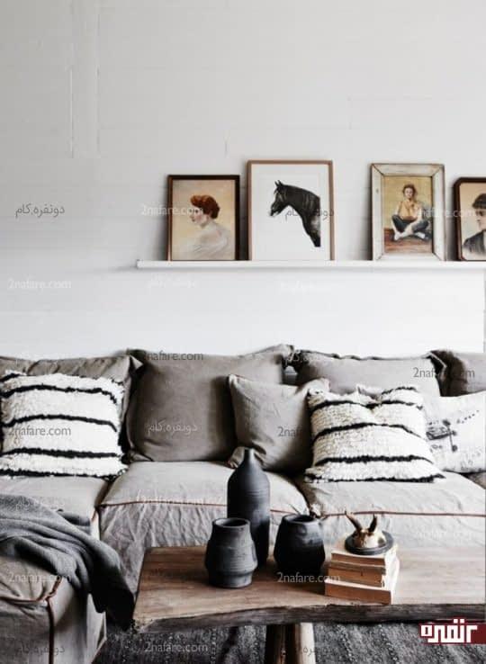 چیدن تابلوهای نقاشی در کنار هم روی قفسه ای دیواری برای تزئین اتاق نشیمن