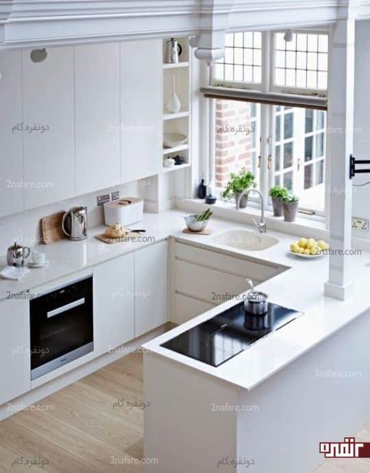 یک آشپزخانه سفید مینیمال با کابینت های براق و یک پنجره بزرگ برای پر کردن فضا با نور