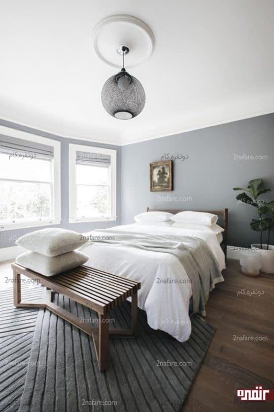 یک اتاق خواب مینیمال با سایه خاکستری و سفید، یک تخت چوبی و نیمکت