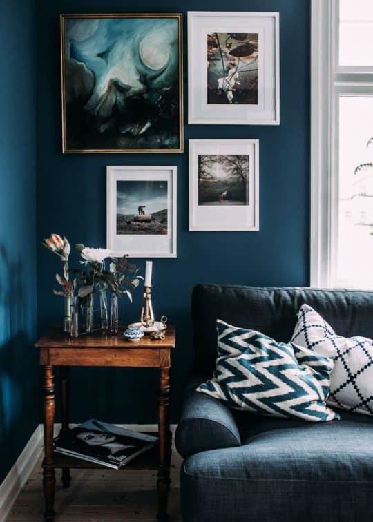 نمایش تابلوهای زیبا با قاب سفید روی دیواری با رنگ آبی تیره