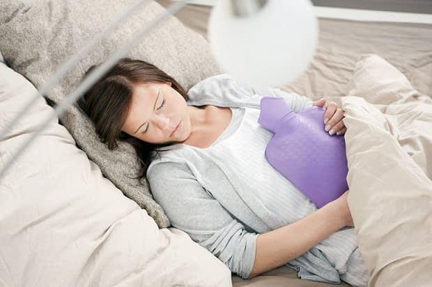 با استفاده از یه کیسه آب گرم شکم و پشت خودتون رو گرم کنین