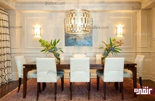 اتاق غذاخوری تزیین شده با تابلویی زیبا و چراغ های دیواری