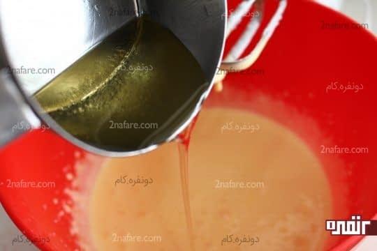 اضافه کردن روغن مایع به مخلوط زرده و شکر