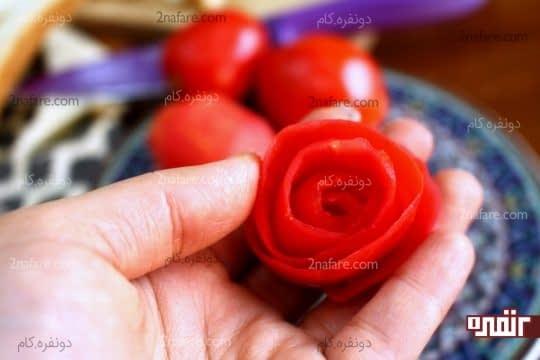 رول کردن پوست گوجه به صورت گل رز