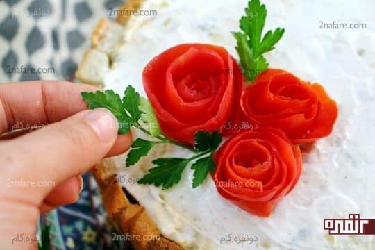 قرار دادن گل های رز گوجه ای و قرار دادن برگ های جعفری روی کیک